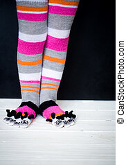 Baby feet in warm, long multicolored socks with toes
