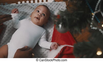 Baby first christmas. Newborn baby admiring christmas tree decoration while playing with father. High quality 4k footage
