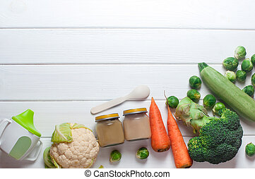 Baby food on the white wooden background