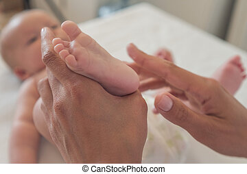 Baby foot massage. Close-up A woman massages the foot of a newborn baby.