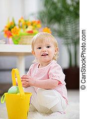 Baby gathering Easter eggs in basket