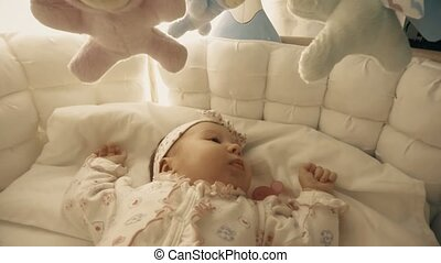 Baby girl about to sleep in her cot - Newborn baby girl in...