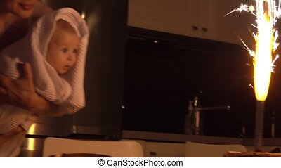 Baby girl and her mom watching birthday cake sparkler