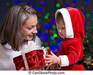 baby girl and her mother holding gift box on bright festive background