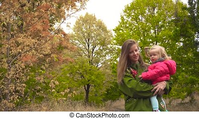 Baby girl and mother in autumn park with colorful trees...