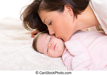 Baby girl and mother kissing her lying happy on white fur ...
