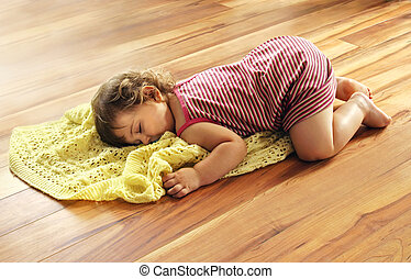 Tired baby girl fallen asleep on wood floor for her afternoon nap