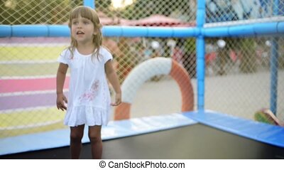 Baby girl at trampoline - Happy child playing at trampoline