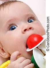 baby girl biting rattle