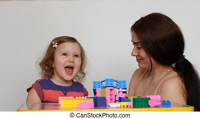 Baby girl capricious and cry, mother tries to calm the baby,...