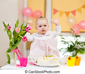 baby girl celebrating first birthday and eating cake