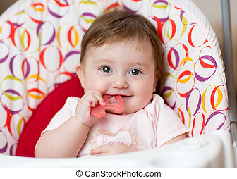 Baby girl chewing on teething toy. First teeth.