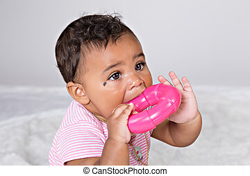 baby girl chewing on toy