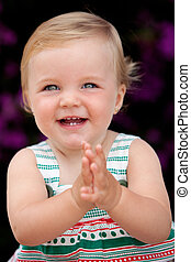 Baby girl clapping with a nice smile on the outside