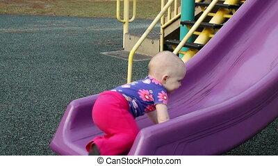 Baby girl climbing up slide