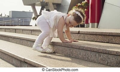 Baby girl climbing up the steps near the shopping center...