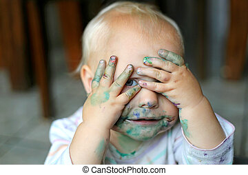 Baby Girl Covered in Paint Hiding Eyes Behind Hands - a cute...