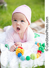Baby girl crawling on the grass with sling beads
