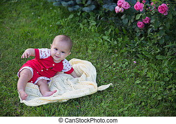Baby girl crawling on the grass with pink flowers