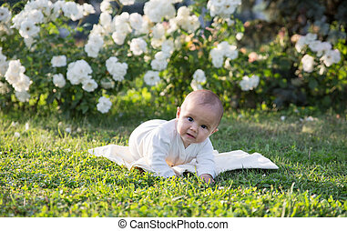Baby girl crawling on the grass with white flowers