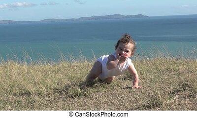 Baby girl crawling outdoors. Baby development concept