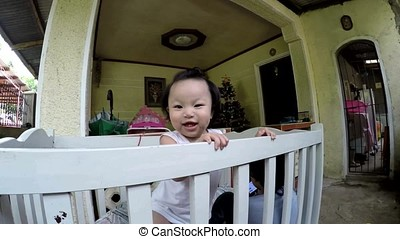 Baby girl creeping and peeping on the railings while playing...