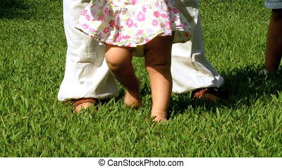Baby girl doing first steps in park