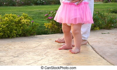 Baby girl doing first steps with mothers help