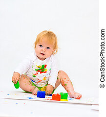 Baby girl drawing picture with paints