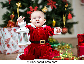 baby girl dressed as Santa Claus at  Christmas tree with lamp