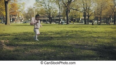 Baby girl dressed in fairy wings playing in the park. Shot...