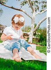 baby girl dressed in white polo and jeans, barefoot sitting with tablet on the fur blanket in the park. Young girl getting into learning on her tablet