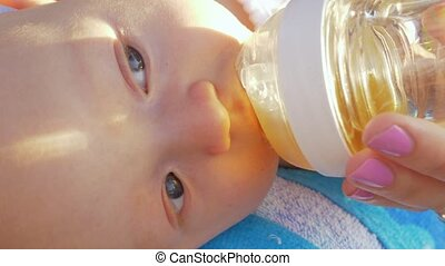 Baby girl drinking from bottle outdoor