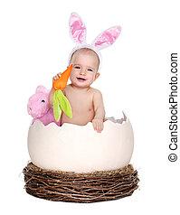 baby girl easter rabbit sitting in a giant easter egg in the nest