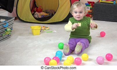 Baby girl eat cookie and play with colorful balls in play room.