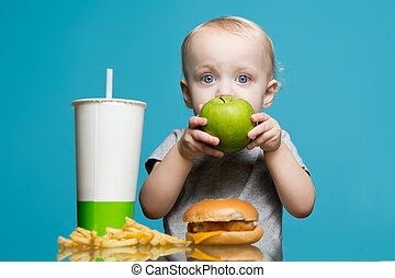baby girl eating an apple, while on the table there was a harmful burger, soda and french fries