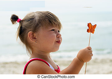 Baby girl eating butterfly lollipop