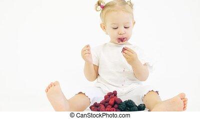Baby girl eating fresh berries on white background - Baby...