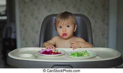 Baby girl eating fruits and vegetables sitting in white high chair 4k