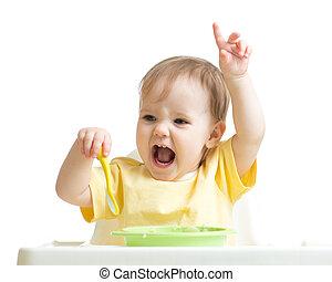 Baby girl eating her dinner isolated on white