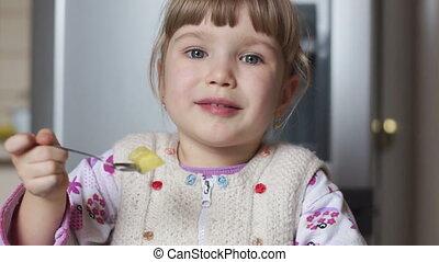 Baby girl eating potatoes in the ki