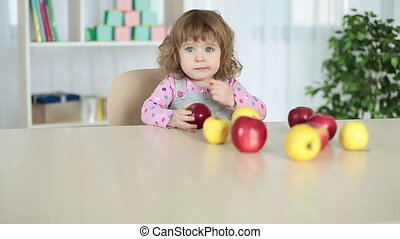 Baby girl eats apples sitting at th