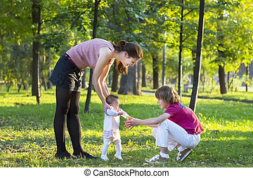 Baby girl first steps with mother and brother in a park
