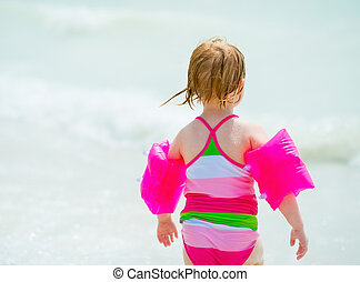 Baby girl going into sea. rear view