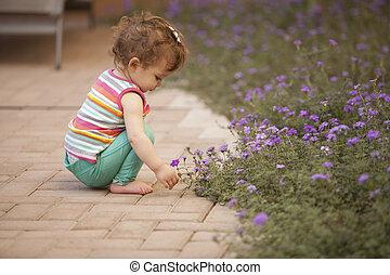 Baby girl having fun in the garden