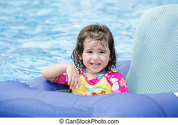 Baby girl having fun on a blue float into a tropical swimming pool