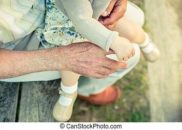 Baby girl holding finger of senior man hand