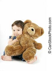 Baby Girl hugging her teddy - a baby girl hugs her teddy and...