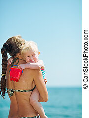 Baby girl hugging mother on beach
