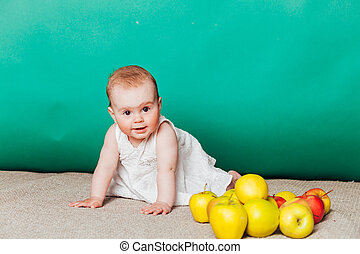 baby girl in a dress with Green apples